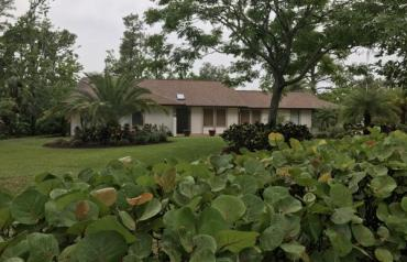 Beautifully landscaped ranch with pool on 1.3 acres near ocean.